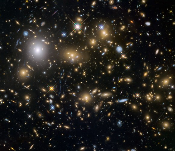 Photo: Hubble Space Telescope image of distant galaxy cluster and gravitational lensing. Credit: NASA/ESA