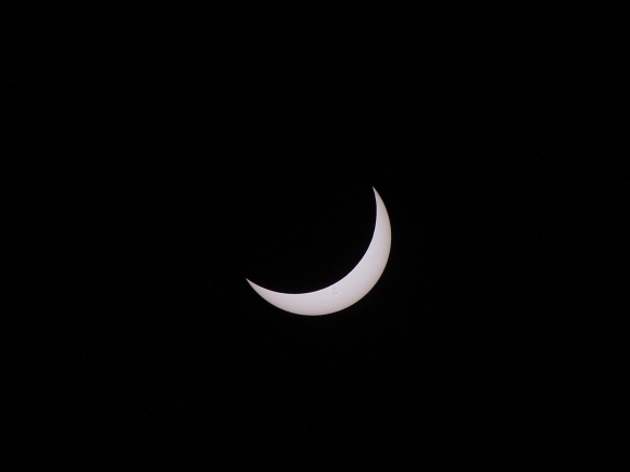 Photo: The partially eclipsed Sun, photographed through a telephoto lens capped with a special-purpose solar filter. The Moon covers 83% of the Sun's diameter and about 79% of its area. Dark sunspots speckle the solar crescent. Credit: Rick Fienberg / TravelQuest International / Wilderness Travel