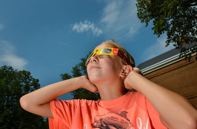 Photo: Girl Watching the Eclipse with Safety Glasses - Credit: Dave Dreimiller