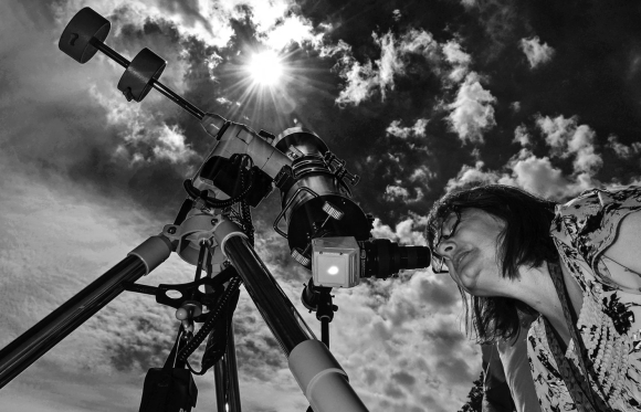 Photo: Woman watches eclipse through specially-equipped telescope. Credit: Dave Dreimiller